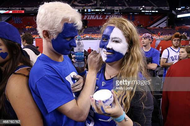 Duke Blue Devils fan paints another fans face before the game against the Wisconsin Badgers during the NCAA Men's Final Four Championship at Lucas...