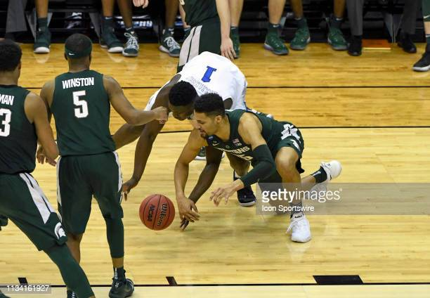 Duke Blue Devils forward Zion Williamson and Michigan State Spartans forward Kenny Goins scramble for a loose ball on March 31 at the Capital One...