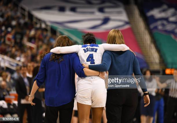 Duke Blue Devils guard Lexie Brown is helped off the court after an injury during the ACC women's tournament game between the NC State Wolfpack and...