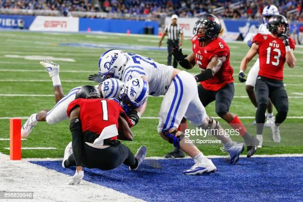 Duke Blue Devils running back Shaun Wilson runs with the ball and runs over Northern Illinois Huskies corner back Albert Smalls to score a touchdown...