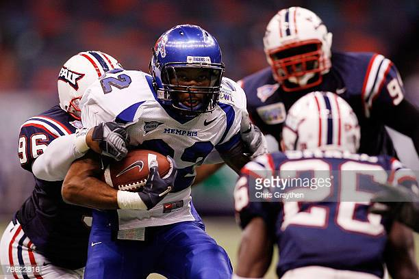 Duke Calhoun of the Memphis University Tigers is tackled by John Mertilus of the Florida Atlantic University Owls in the RL Carriers New Orleans Bowl...