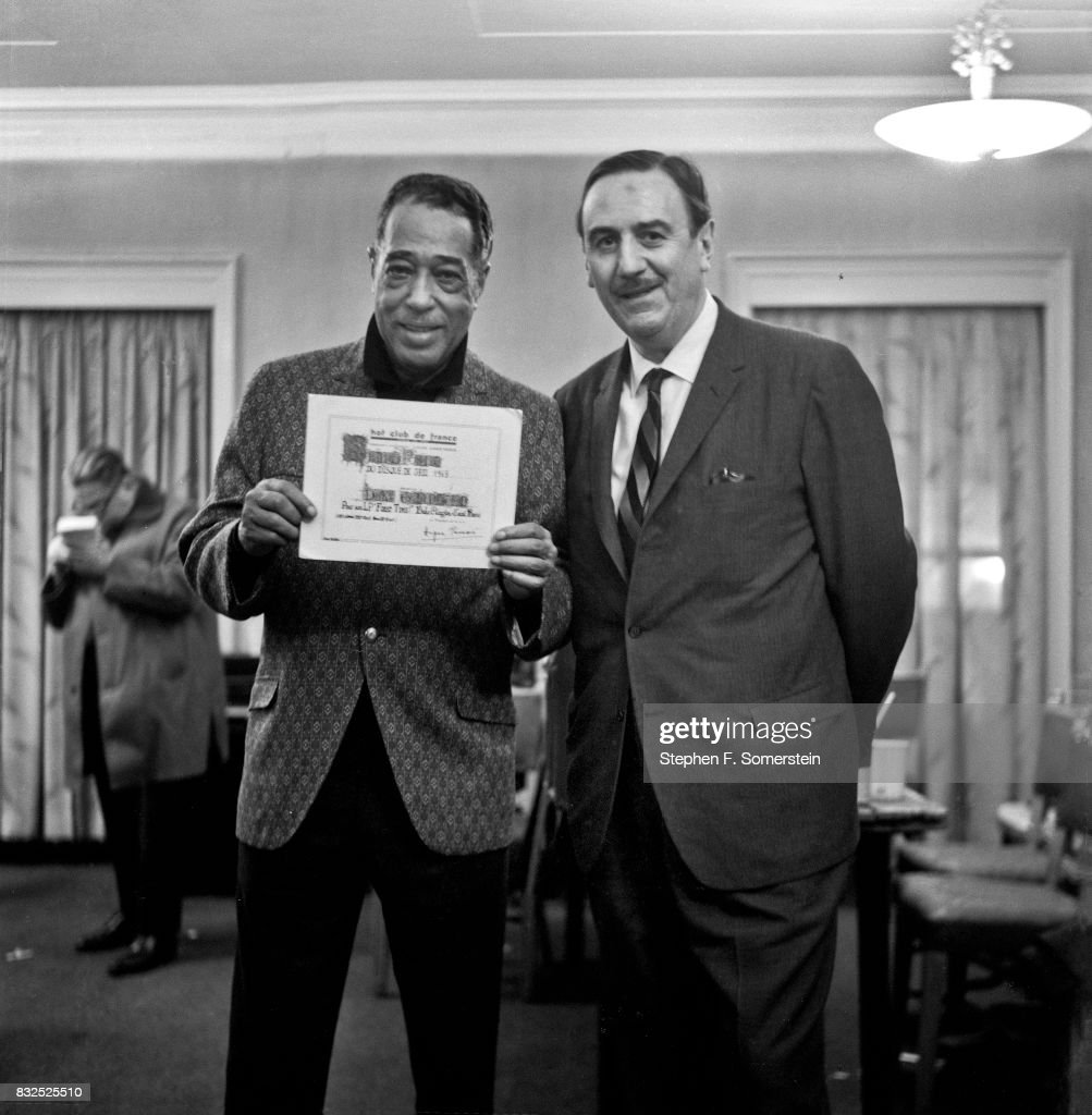 Duke Ellington holding award plaque given to him by Hot Club de France magazine. Biographer, Stanley Dance on right. Shelton Towers Hotel in 1963 in New York City, New York.