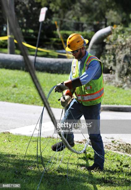 A Duke Energy contractor coils downed power lines on Dommerich Drive during the first stage of assessment and restoration in the aftermath of...