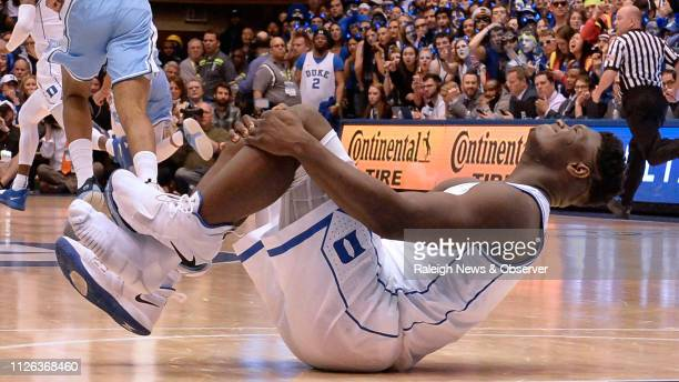 Duke forward Zion Williamson holds his knee after injuring himself and damaging his shoe during the opening moments of the game in the first half on...