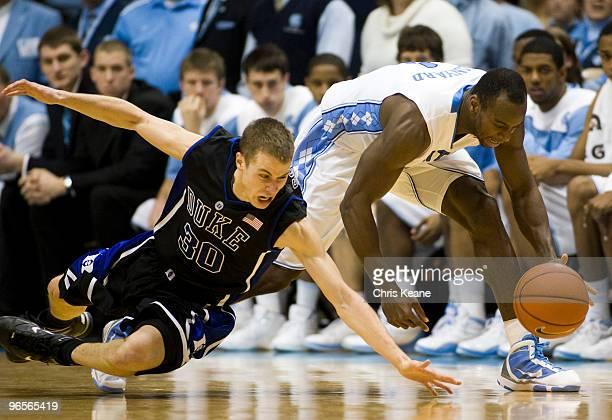 Duke guard Jon Scheyer dives for a loose ball against North Carolina guard/forward Marcus Ginyard during a men's college basketball game at Dean...