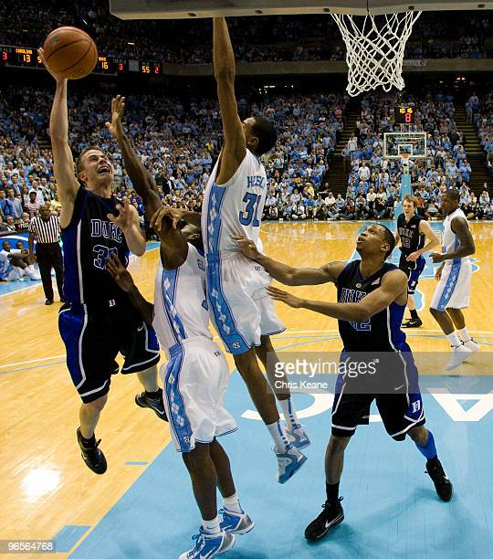 Duke guard Jon Scheyer shoots around North Carolina forward John Henson during a men's college basketball game at Dean Smith Center on February 10,...