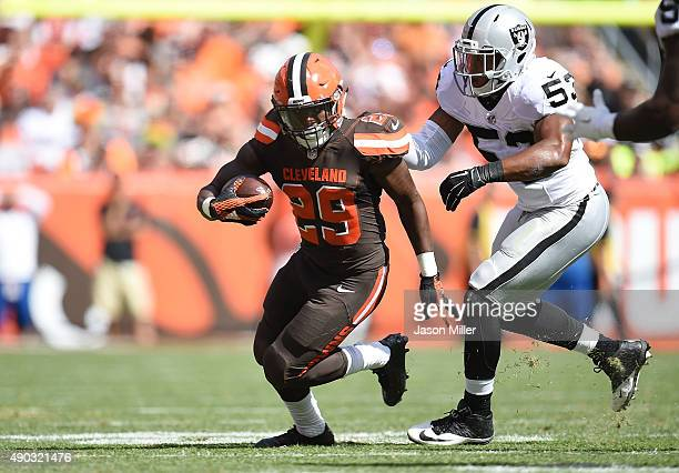 Duke Johnson of the Cleveland Browns carries the ball in front of the defense of Malcolm Smith of the Oakland Raiders during the second quarter at...