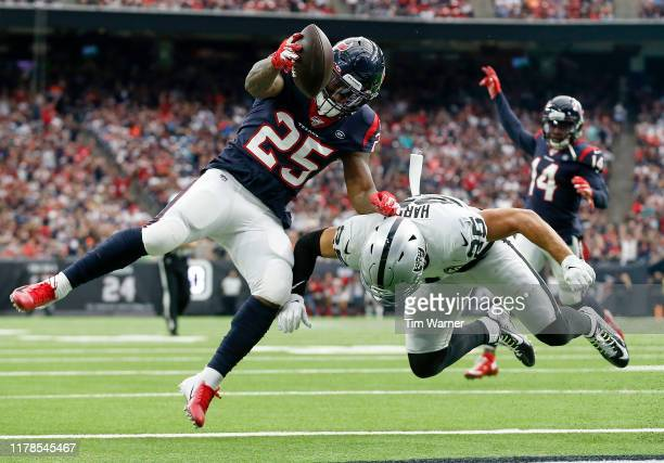 Duke Johnson of the Houston Texans scores a touchdown defended by Erik Harris of the Oakland Raiders in the second quarter at NRG Stadium on October...