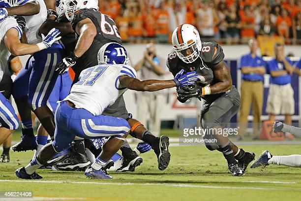 Duke Johnson of the Miami Hurricanes scores a first quarter touchdown past the defense of DeVon Edwards of the Duke Blue Devils on September 27 2014...