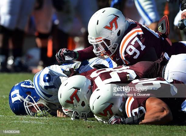 Duke quarterback Sean Renfree lies under a pile of Virginia Tech defenders after being sacked in the second half of play The Virginia Tech Hokies...