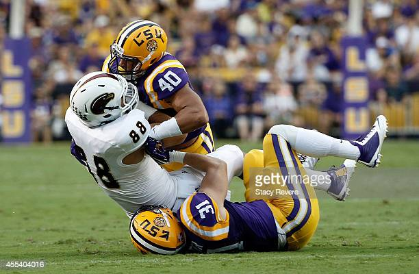 Duke Riley and DJ Welter of the LSU Tigers bring down Harley Scioneaux of the Louisiana Monroe Warhawks during the first quarter of a game at Tiger...