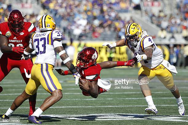 Duke Riley and Jamal Adams of the LSU Tigers chase down Lamar Jackson of the Louisville Cardinals in the third quarter of the Buffalo Wild Wings...