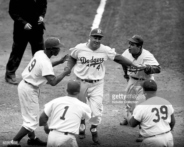 Duke Snider is greeted at home plate by teammates Jim Gilliam Pee Wee Reese Roy Campanella and the batboy of the Brooklyn Dodgers after homering in a...