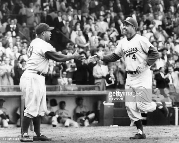 Duke Snider of the Brooklyn Dodgers is congratulated by teammate Roy Campanella after Snider hit a homerun during the 1955 World Series against the...