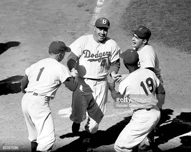 Duke Snider of the Brooklyn Dodgers is greeted at home plate by teammembers Jim Gilliam Pee Wee Reese and the batboy after homering in World Series...