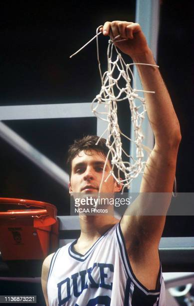 Duke University forward Christian Laettner holds up the net after his team's 7151 victory over the University of Michigan which earned Duke the NCAA...