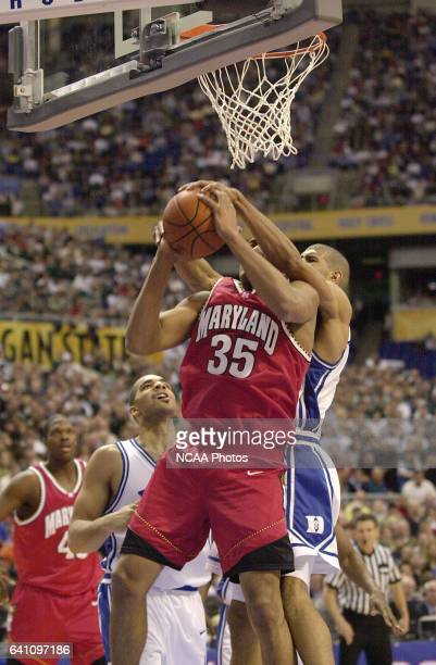 Duke University forward Shane Battier reaches around from behind on University of Maryland forward/center Lonny Baxter to win a jump ball call during...