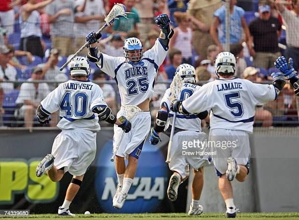 Duke University's Matt Danowski midfielder Terrence Molinari and midfielder Peter Lamade charge teammate Zack Greer after he scored the winning goal...