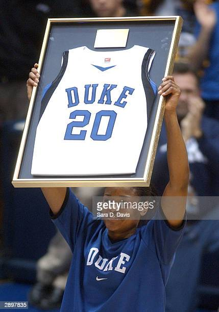 Duke's Alana Beard raises up her framed jersey number after an official ceremony retiring her jersey before the game against Tennessee in Cameron...