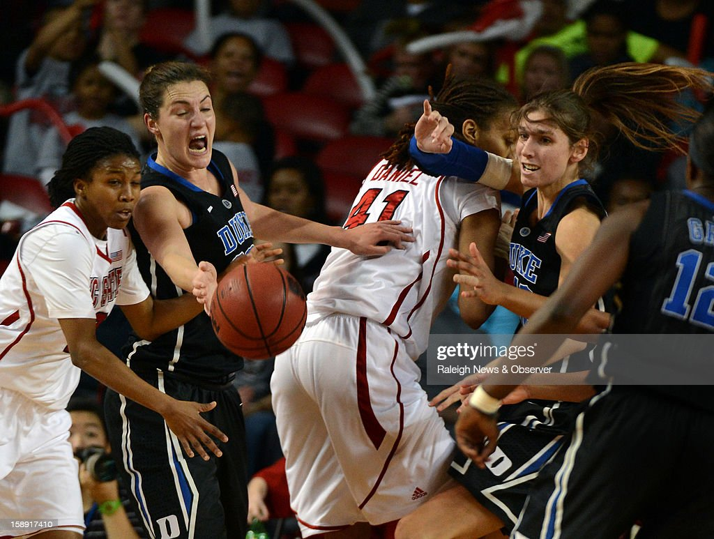 Duke's Haley Peters (33) has the ball knocked away by North Carolina State's Len'Nique Brown (2) in the first half at Reynolds Coliseum in Raleigh, North Carolina, on Thursday January 3, 2013.