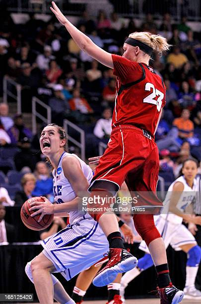 Duke's' Haley Peters left looks to the basket around Nebraska's Emily Cady during Sunday's NCAA women's basketball regional semifinal on March 31 at...