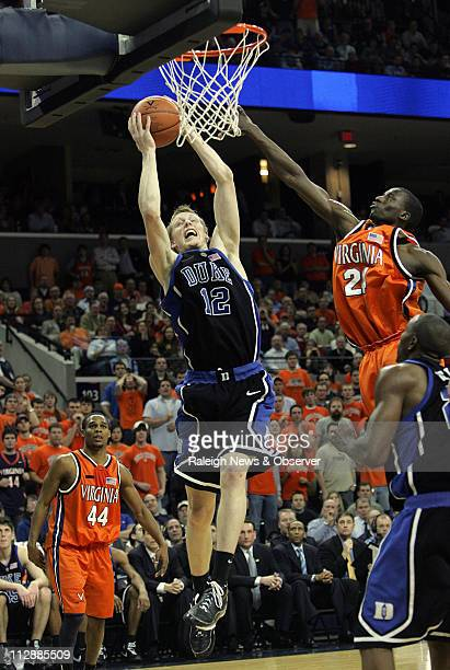 Duke's Kyle Singler drives to the basket between Virginia's Sean Singletary and Mamadi Diane during second half action The Blue Devils defeated the...