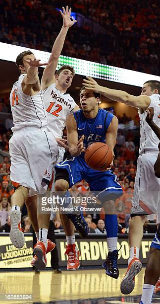 Duke's Seth Curry is surrounded by Virginia defenders as he moves inside during the second half at John Paul Jones Arena in Charlottesville Virginia...