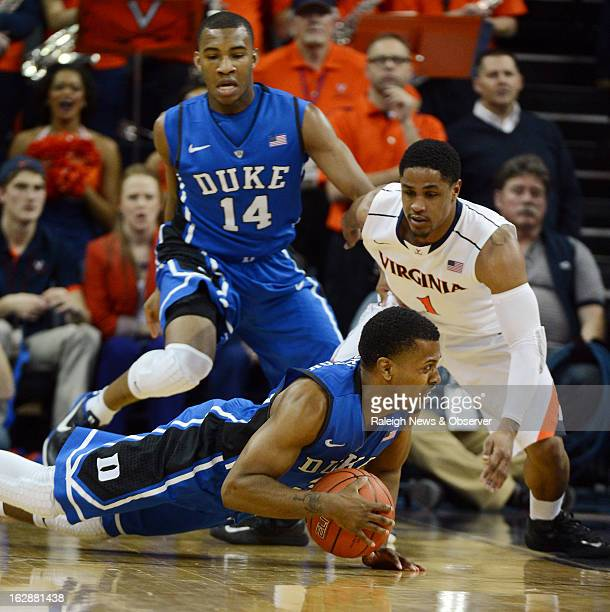 Duke's Tyler Thornton tries to save a ball as Virginia's Jontel Evans defends in the first half at John Paul Jones Arena in Charlottesville Virginia...