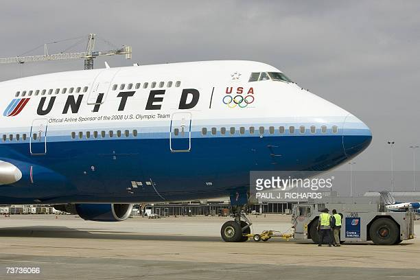 Ground crew members for United Airlines flight at Washington DC's Dulles International Airport release the aircraft from push back 28 March 2007 as...
