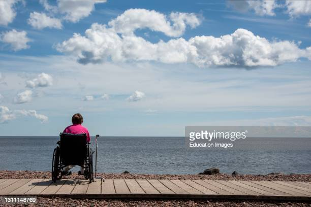 Duluth, Minnesota, A 67 year old woman in a wheelchair sits alone looking out over Lake Superior.