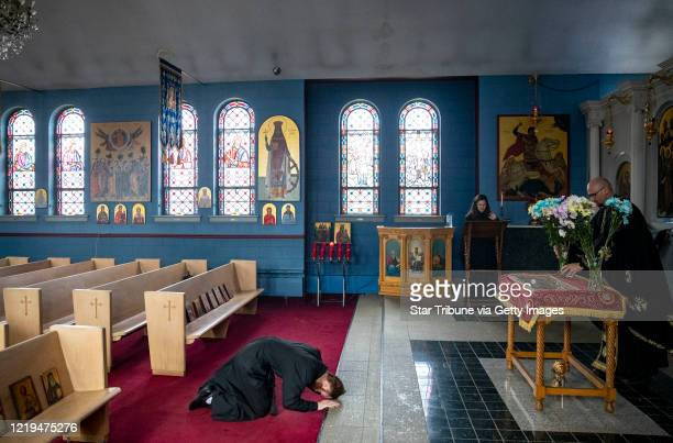 Steven Thell, the acolyte helping with services on Good Friday, bowed before the burial shroud while Father Timothy Sas places flowers atop it during...