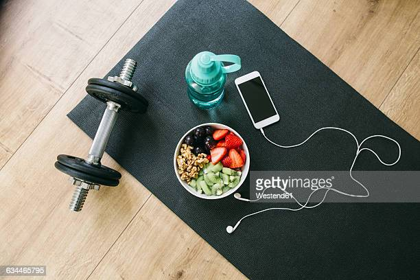 dumbbell, drinking bottle, fruit bowl and smartphone with earphones - colchoneta de ejercicio fotografías e imágenes de stock