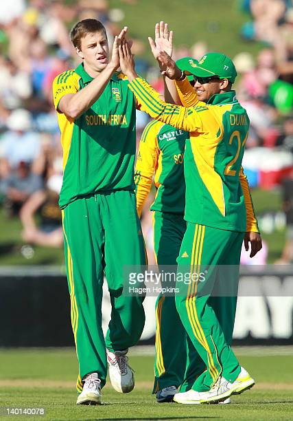 Duminy of South Africa congratulates teammate Morne Morkel on the wicket of Tarun Nethula of New Zealand during the One Day International match...