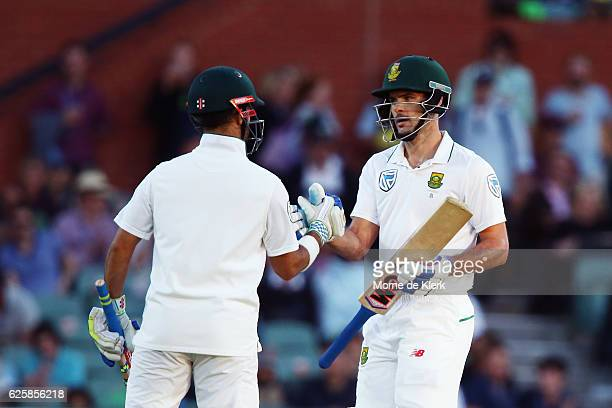 Duminy of South Africa congratulates teammate Stephen Cook after he reached 50 runs evades a high ball during day three of the Third Test match...