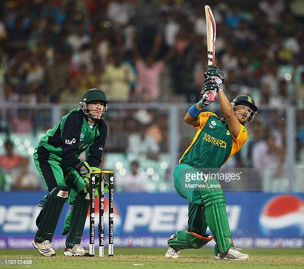 Duminy of South Africa hits the ball towards the boundary as Niall O'Brien of Ireland looks on during the 2011 ICC World Cup Group B match between...