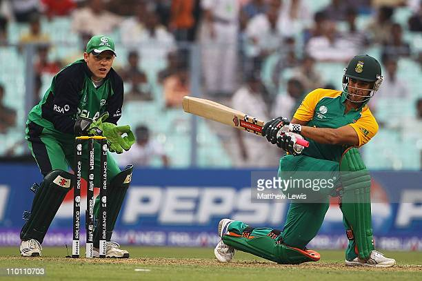 Duminy of South Africa plays a sweep shot as Niall O'Brien of Ireland looks on during the 2011 ICC World Cup Group B match between Ireland and South...