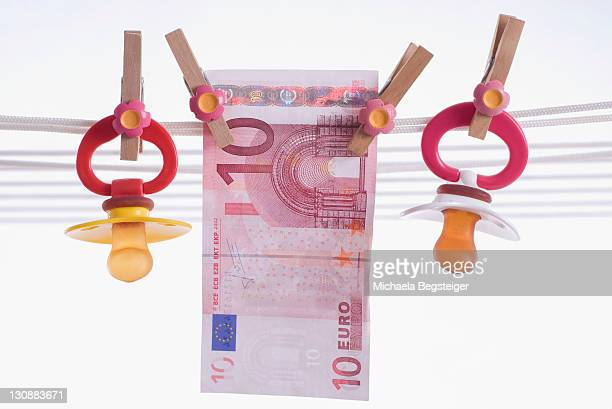 Dummy and banknote on a washing line, symbolic picture for child benefit