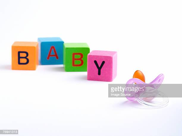 Dummy and building blocks spelling baby