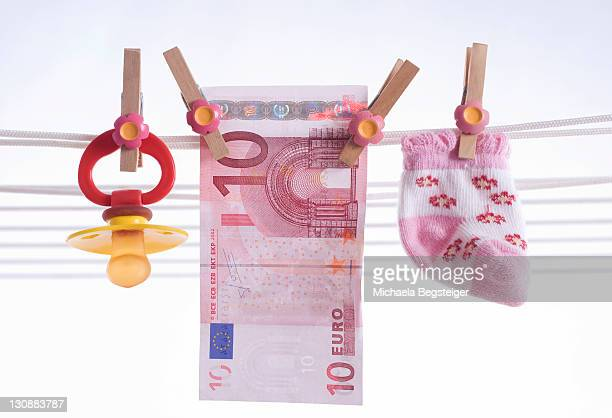 Dummy, baby socks and banknote on a washing line, symbolic picture for child benefit