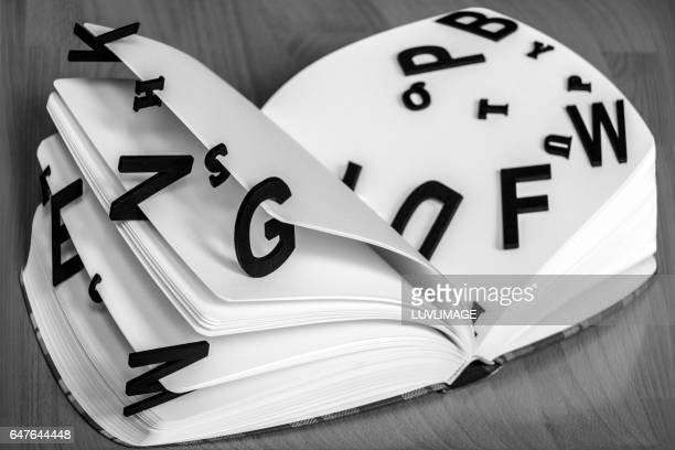 dummy book with black letters loosely on the pages. - typographies stock photos and pictures