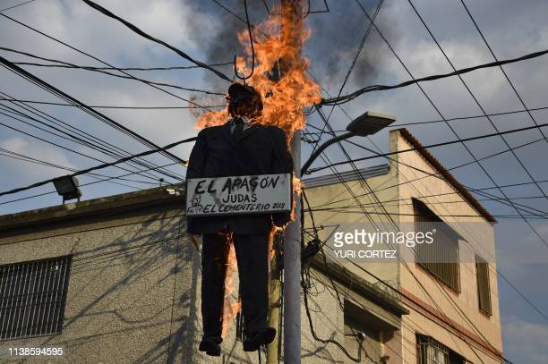 TOPSHOT A dummy depicting 'The Blackout' burns in flames after being set on fire by supporters of Venezuelan President Nicolas Maduro during the...