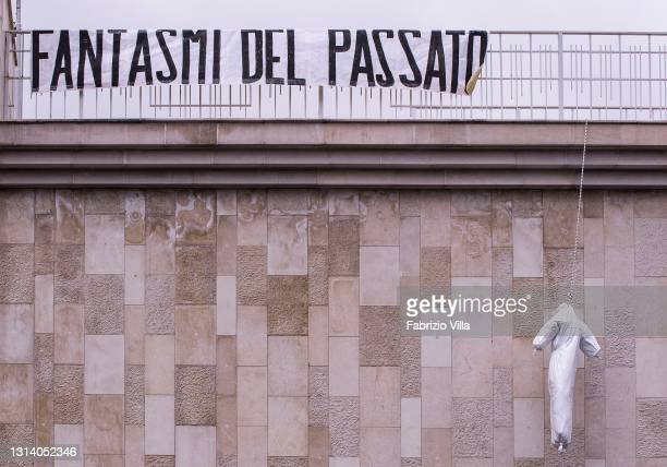 """Dummy hanged by the """"Ghosts of the past"""", including restaurateurs, VAT numbers and gym owners gathered for a flash mob protest, wearing white masks..."""