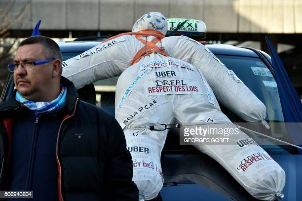 A dummy is fixed to the hood of a taxi car as taxi drivers block a street near the Prefecture in Bordeaux southwestern France on January 26 to...