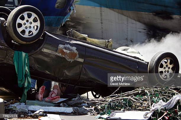 A dummy victim lies under a car in the crash zone during an exercise simulating mass casualties from the collision between a singleengine Cessna and...