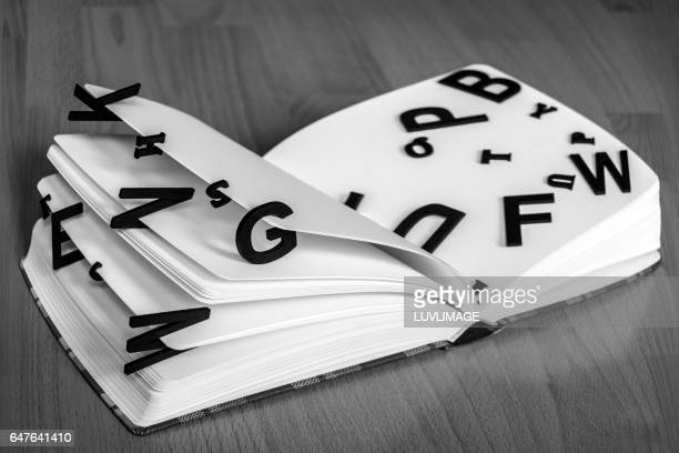 dummybook with random black letters floating on pages. - typographies stock photos and pictures