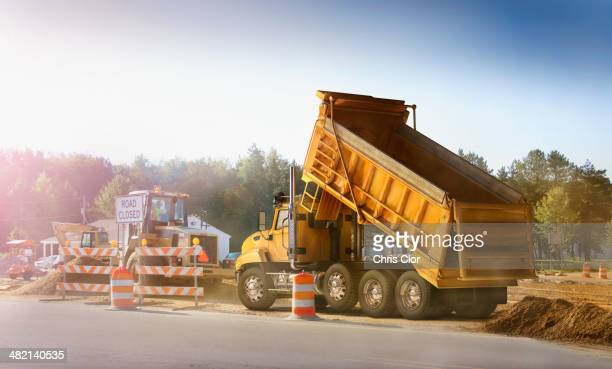 dump truck dumping haul on site - dump truck stock pictures, royalty-free photos & images