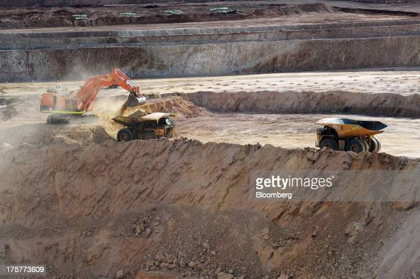 A dump truck is loaded with ore in the openpit mine as another truck approaches at the Norton Gold Fields Ltd Enterprise operations 68 kilometers...