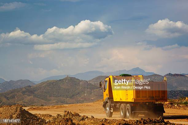 Dump Truck Laden With Earth Driving On Construction Site
