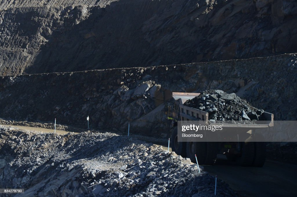 A dump truck laden with ore drives out of the White Foil open mine pit at Evolution Mining Ltd.'s gold operations in Mungari, Australia, on Tuesday, Aug. 8, 2017. Evolution Mining is Australias second-largest gold producer. Photographer: Carla Gottgens/Bloomberg via Getty Images