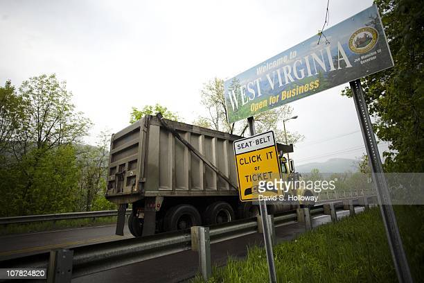 A dump truck passes a state line sign which reads Welcome to West Virginia Open for Business on the way into Keyser West Virginia on May 1 2008